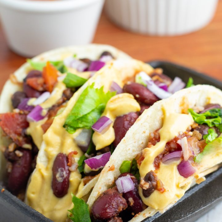 3 tacos stuffed with vegetables and standing in black cast iron pan