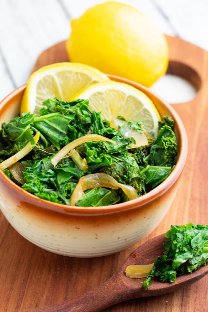 braised kale in brown and white bowl with lemon slices