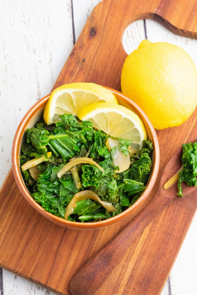 overhead shot of cooked kale in brown bowl on cutting board with lemon