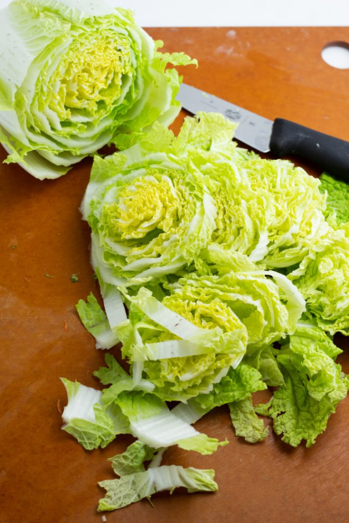 napa cabbage on cutting board with knife