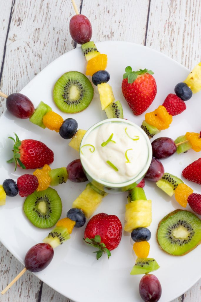 fruit skewers on white plate in a burst position