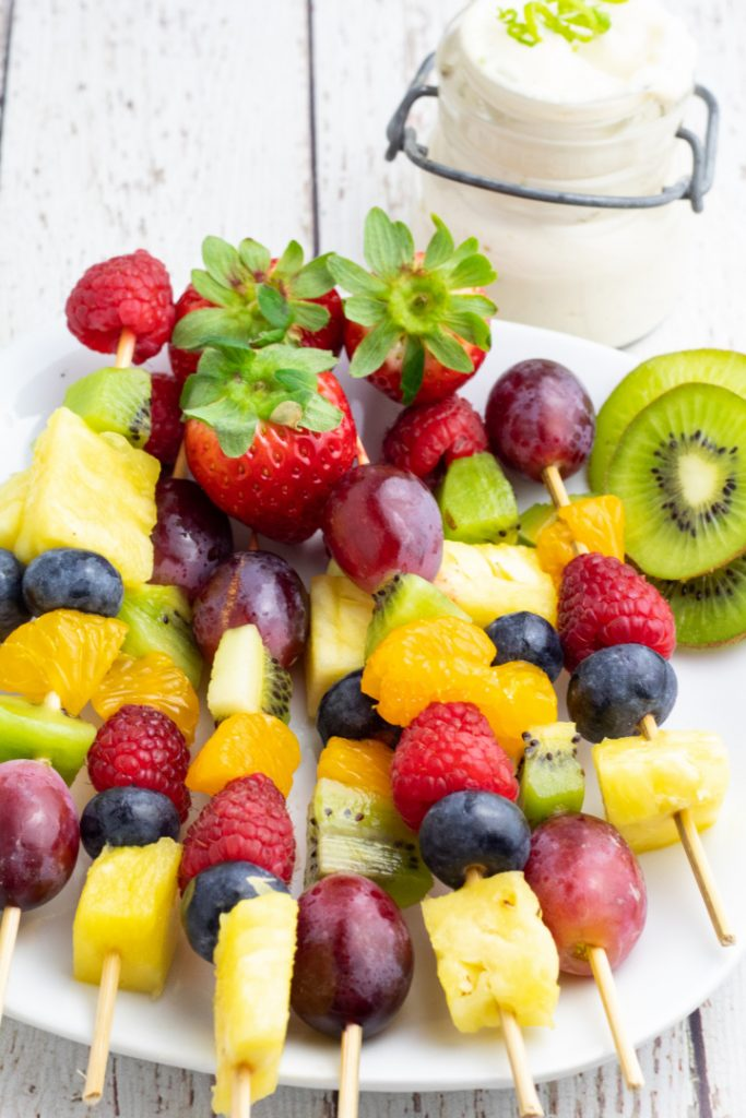 fruit skewers piled up on white plate