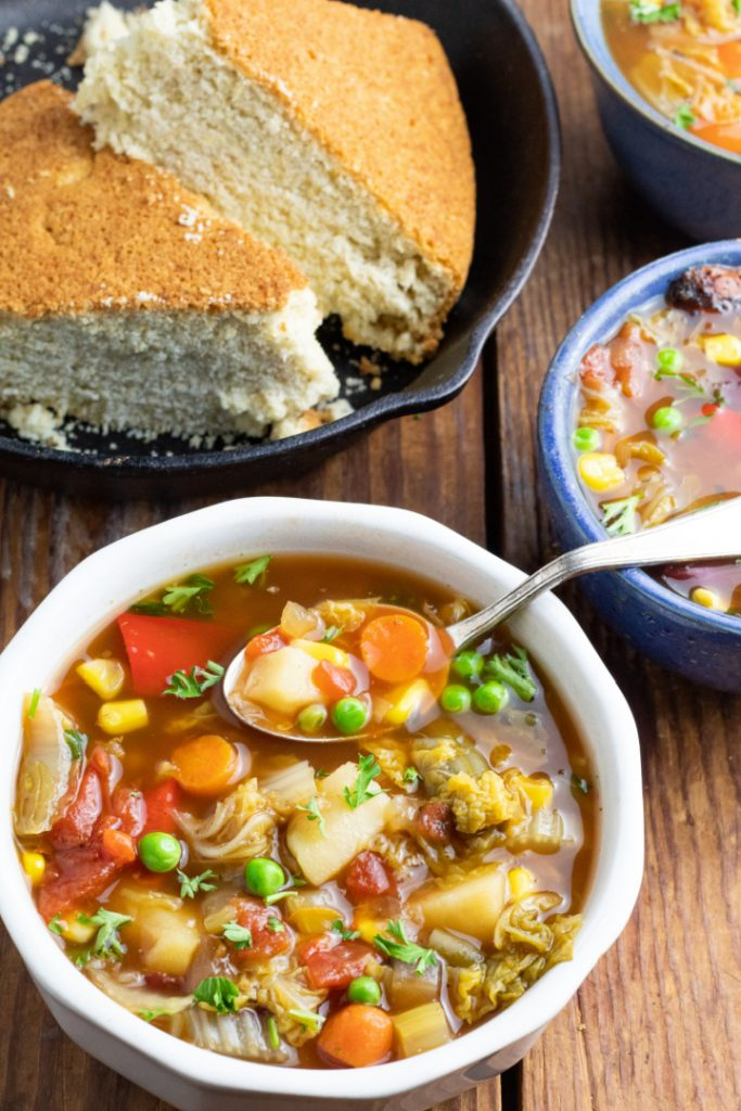 white bowl full of vegetable soup with spoon and cornbread