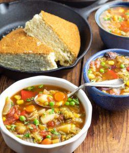 white bowl full of vegetable soup with spoon and cornbread in cast iron skillet