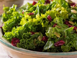 kale salad with raisins in bowl