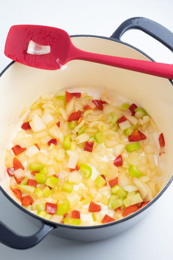 sauteed onions, celery, and red bell pepper in large stockpot with red spatula