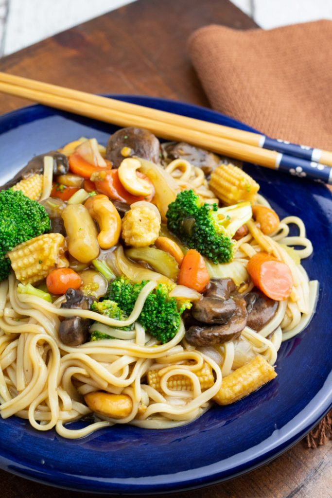 udon noodle stir fry in bright blue plate with chopsticks on side