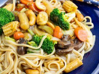 udon veggie stir fry on bright blue plate