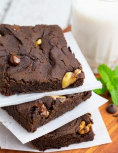 black bean brownies sliced and stacked on parchment paper