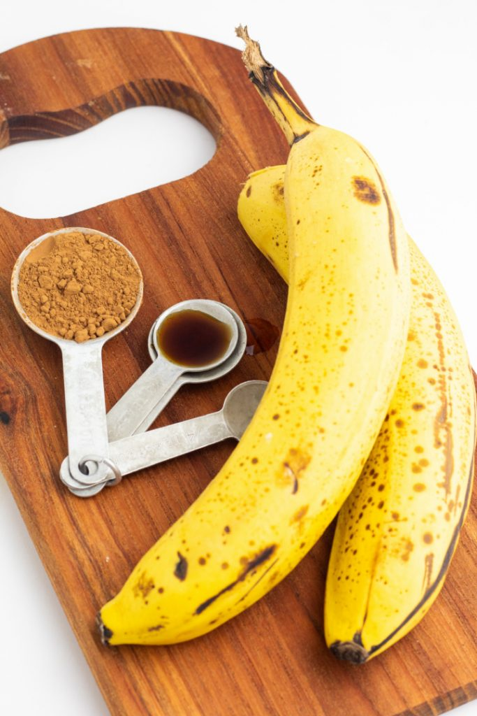 2 ripe bananas and coco on a brown board