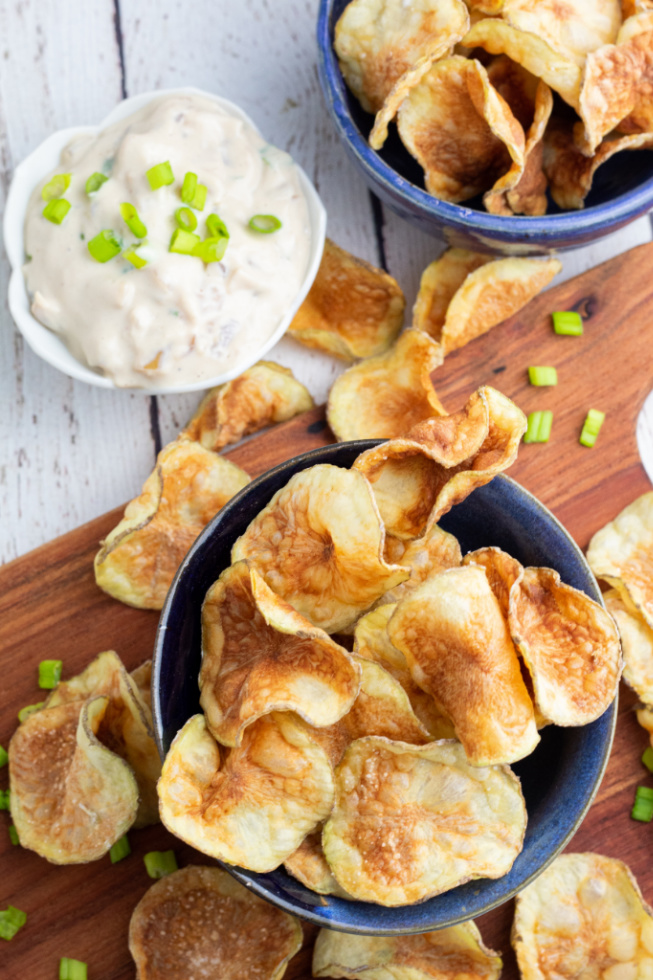 overhead photo of homemade potato chips in two blue bowls with dip