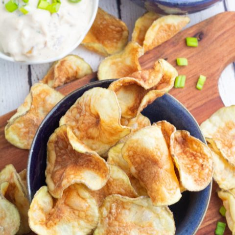 crispy homemade potato chips in blue bow with dip in background