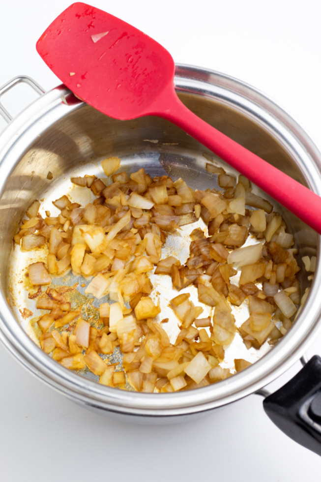 stainless saucepan with sauteed onions and spatula