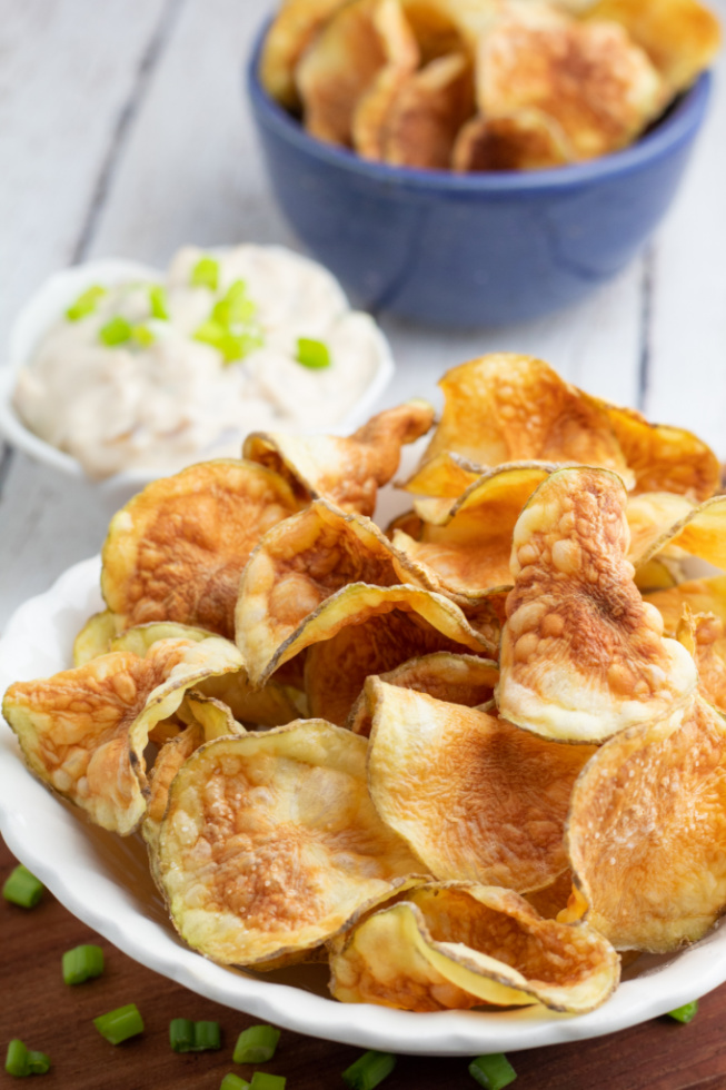 white bowl filled with crunchy potato chips and blue bowl full in background