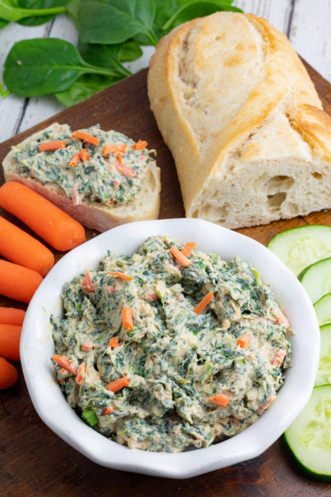 overhead photo of spinach dip on brown board with bread and veggies