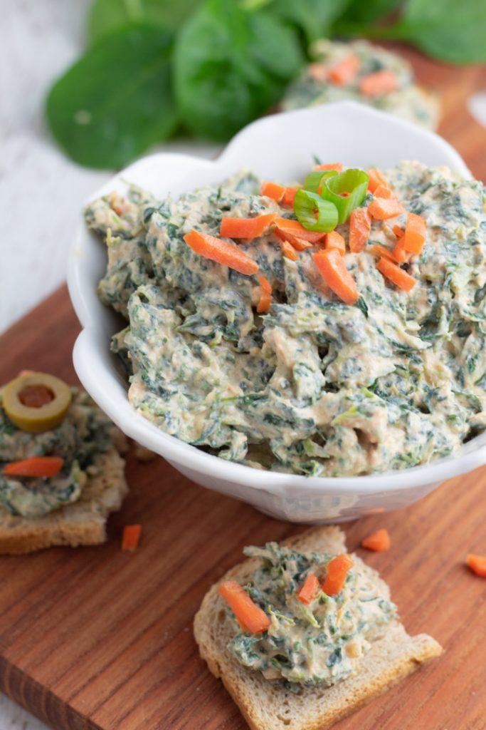 spinach dip in white flowery bowl topped with shredded carrots