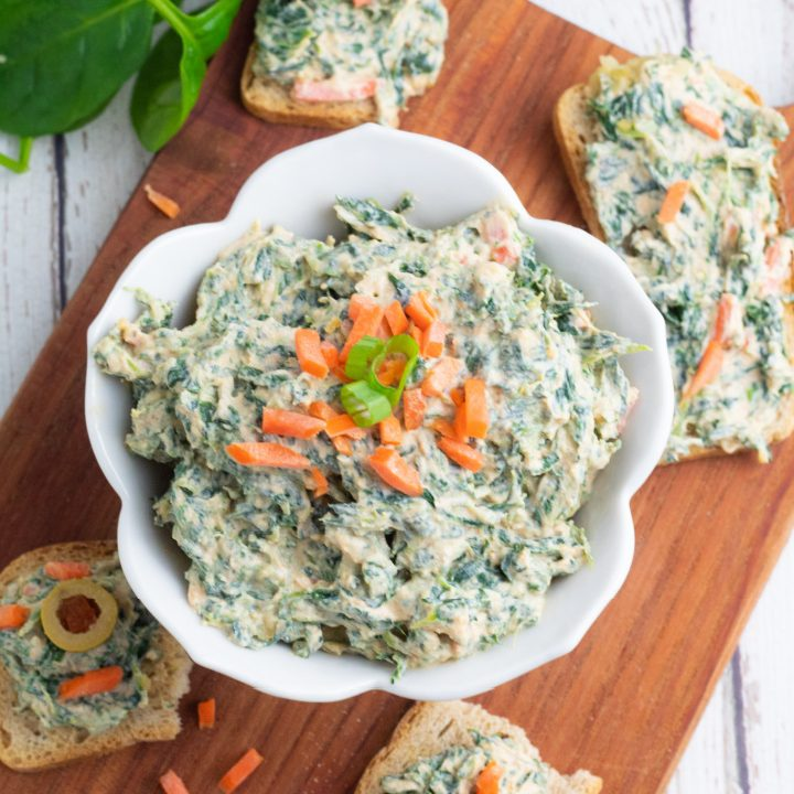 overhead photo of vegan spinach dip in white bowl with crackers