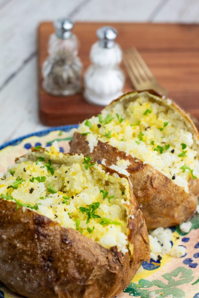 two baked potatoes topped with salt, spices, and fresh parsley