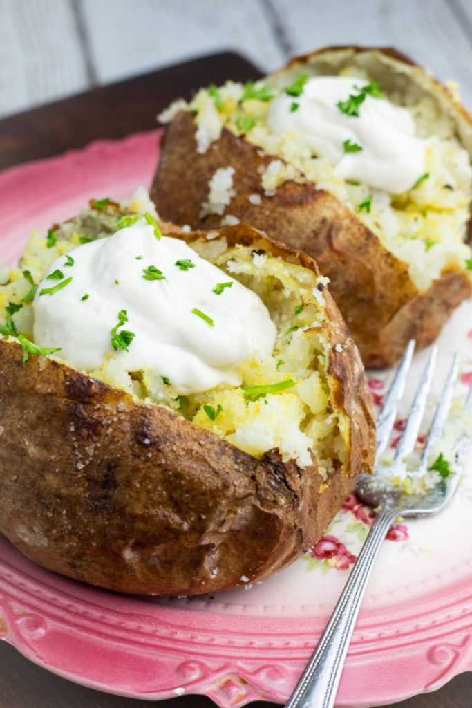 two air fryed baked potatoes topped with vegan sour cream and parsley
