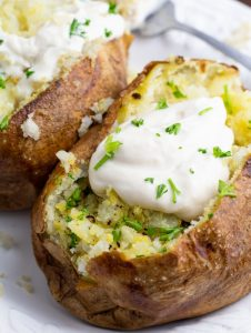 close up of two air fryed baked potatoes topped with vegan sour cream on white plate