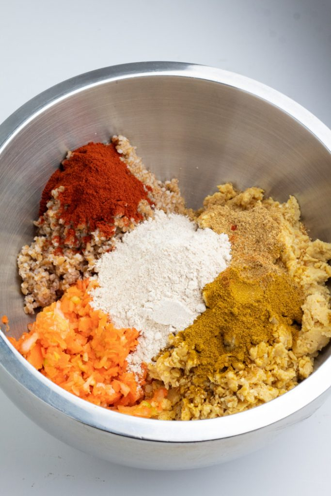 mixing bowl with chickpeas, veggies, bulgur, and spices