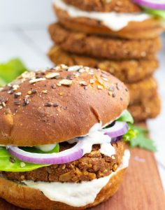 chickpea burger with lettuce, onions, vegan mayo and chickpea patties stacked in background