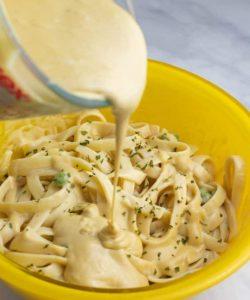vegan alfredo sauce being poured on pasta