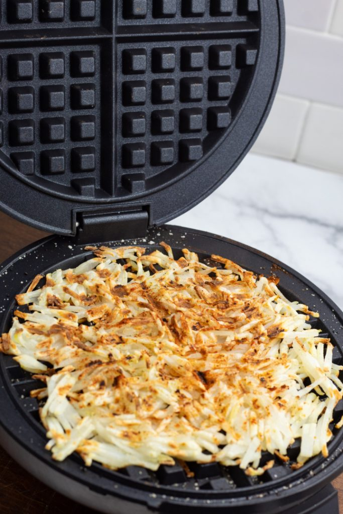 cooked crispy hash browns in waffle iron with lid raised