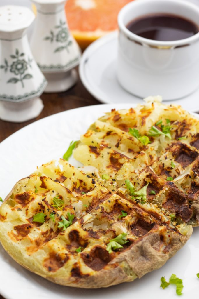 baked potato cooked in waffle iron on white plate with coffee