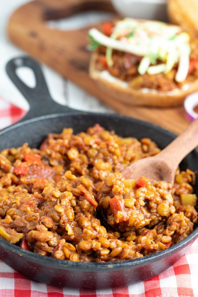 cast iron skillet filled with seasoned lentils and wooden spoon