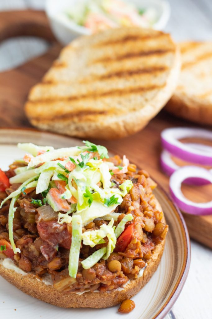 open lentil sloppy joe sandwich topped with slaw and toasted bun in background