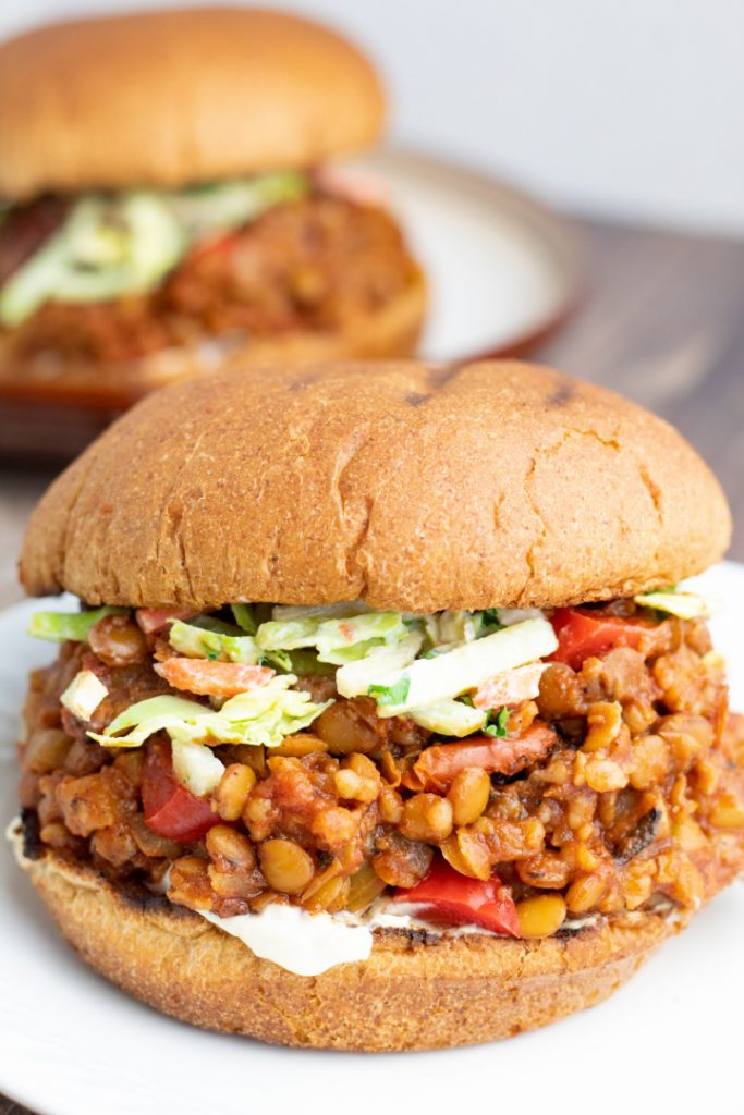 close up of lentil sloppy joe topped with slaw