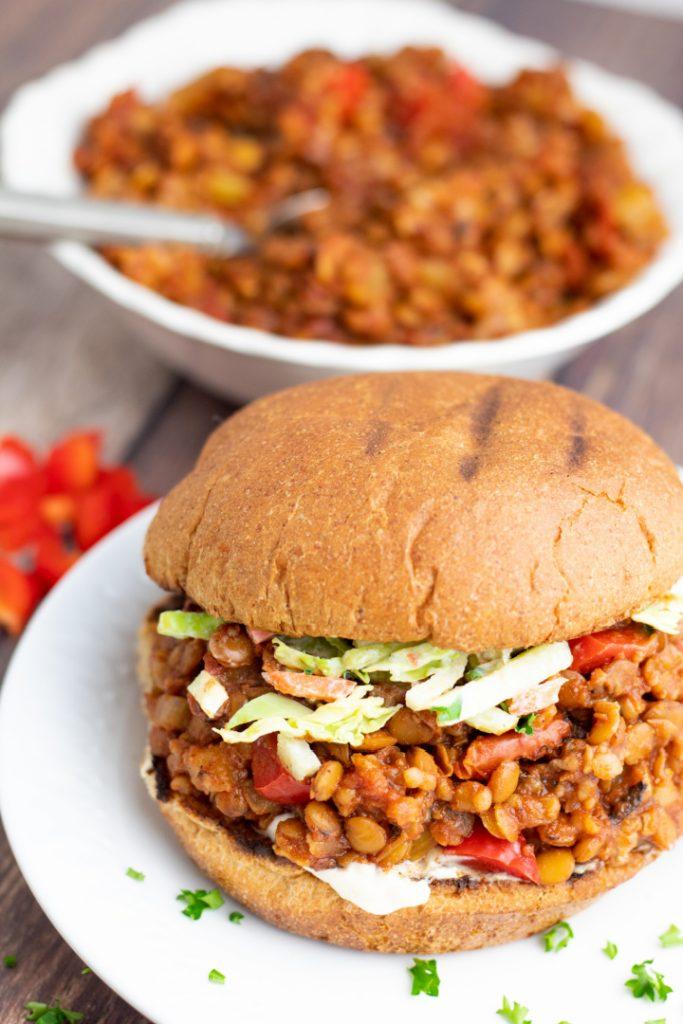 veggie lentil sloppy joe on white plate with bowl of lentils in background