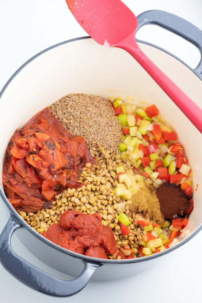 large blue stockpot filled with lentils, tomatoes, vegetables, bulgur, and spices