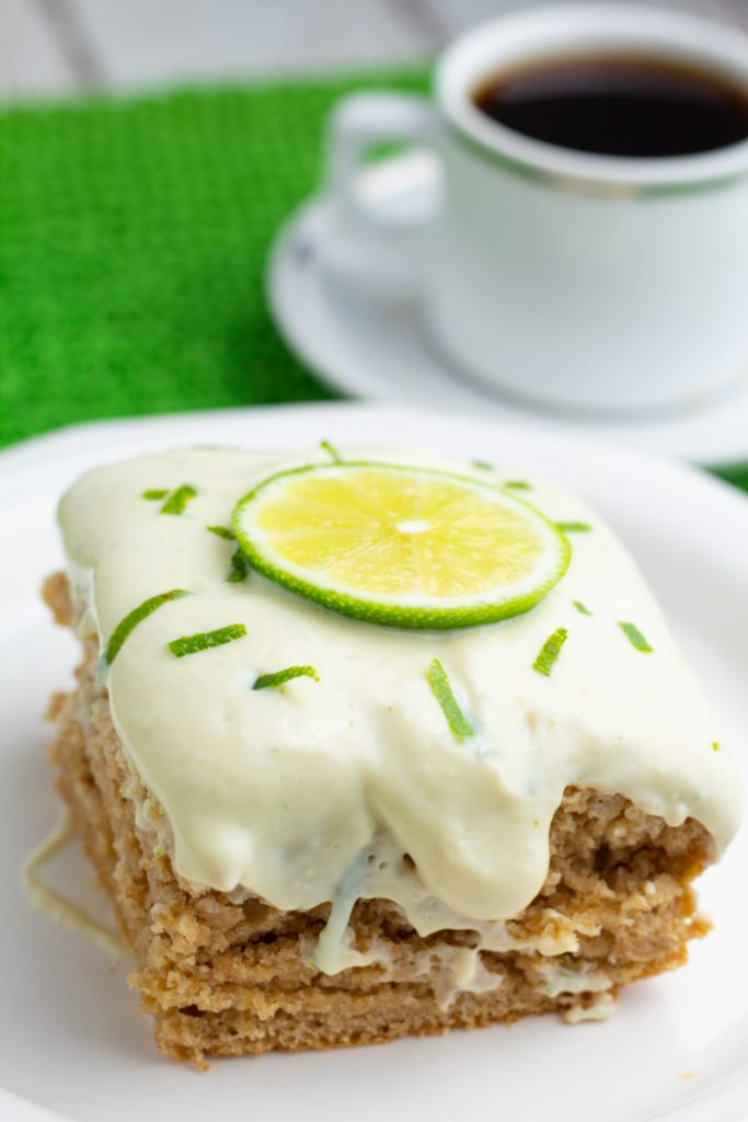 close up of lime cake with white lime frosting and topped with lime slice