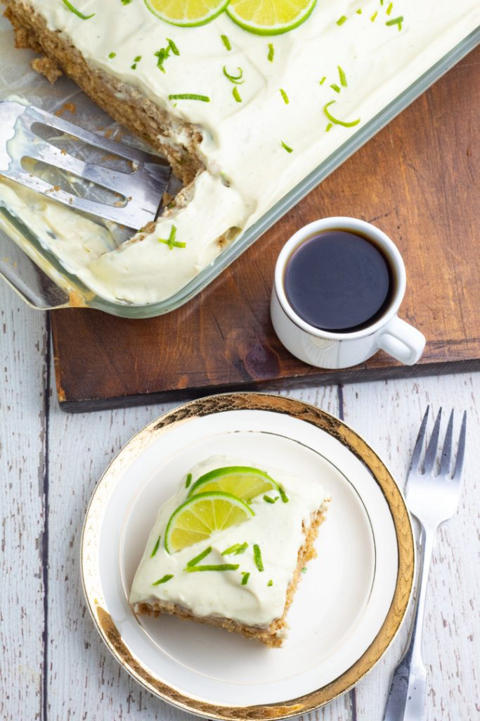 overhead photo of a slice of cake on fancy plate with cup of coffee
