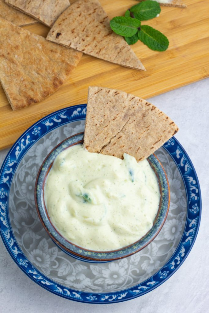 bright blue bowl with tzatziki sauce and pita bread