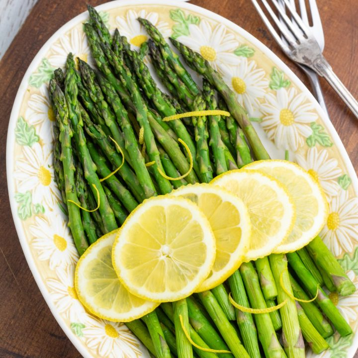 air fryer asparagus in oval plater topped with lemon slices