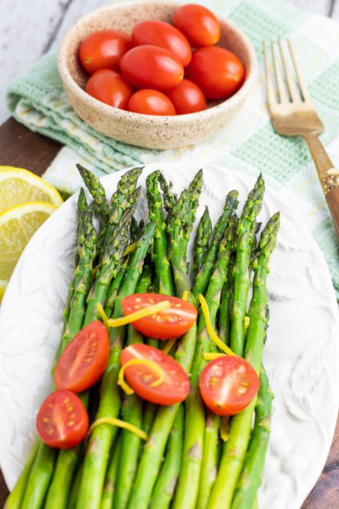white plate with air fried asparagus with cherry tomatoes