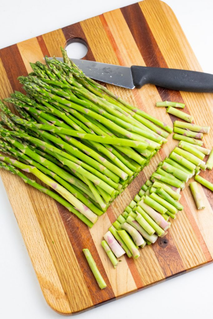 raw asparagus on cutting board with bottoms chopped off and knife