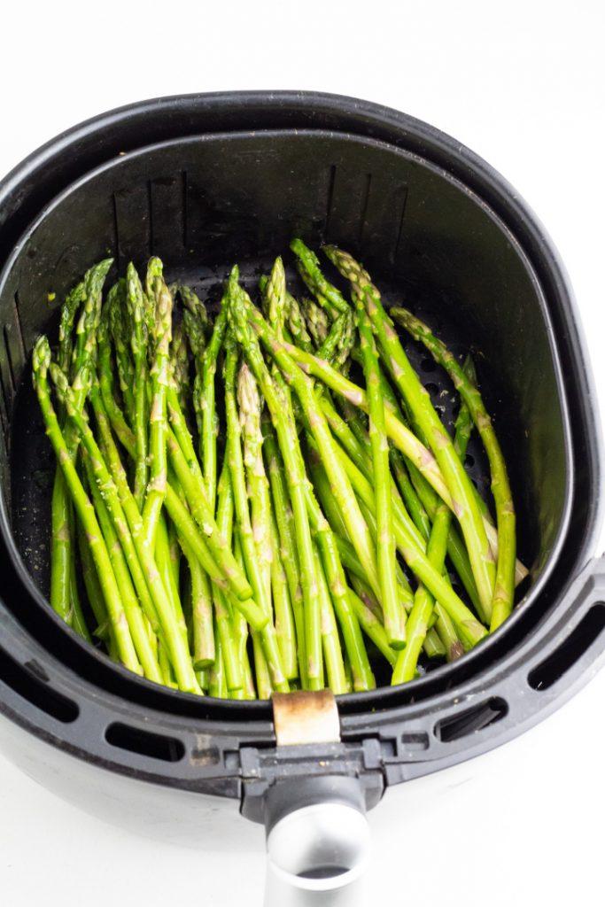 air fryer basket full of asparagus spears