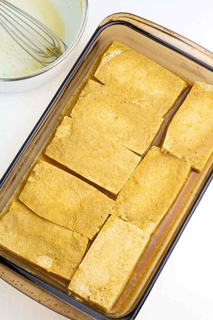 tofu slices marinating in a flat baking dish