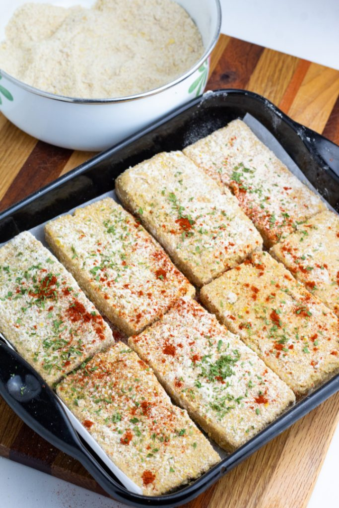 slices of battered tofu on baking sheet with spices