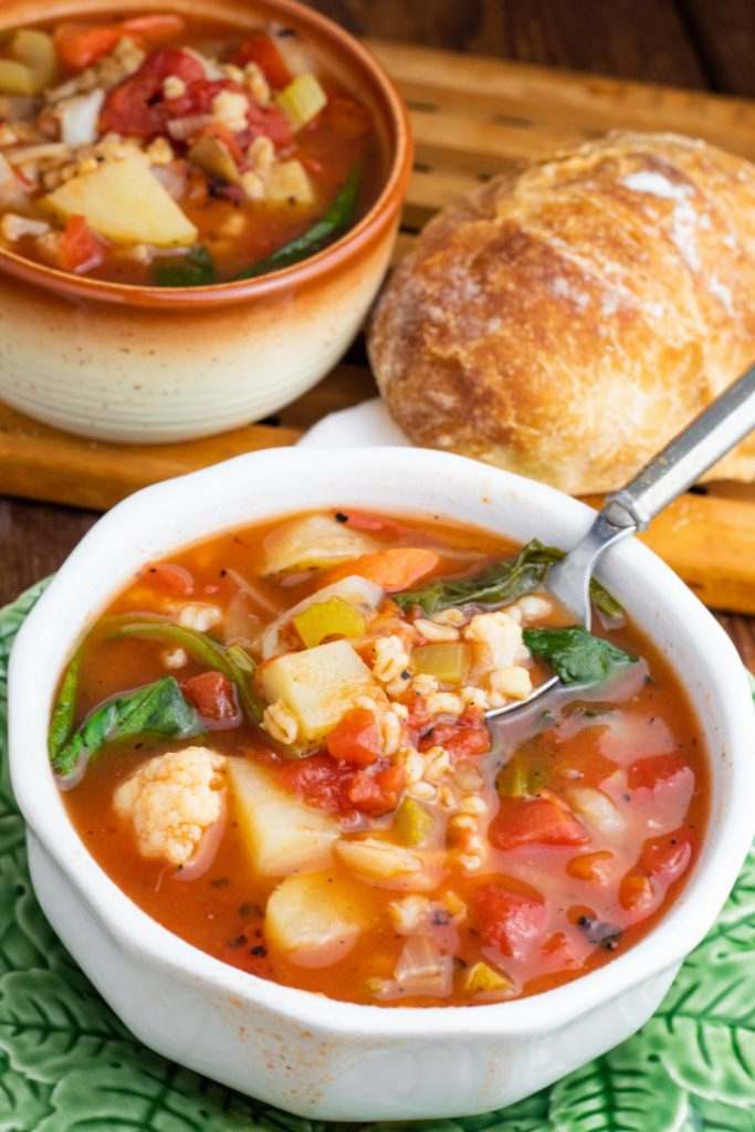 white bowl of barley vegetable soup and spoon with crusty bread