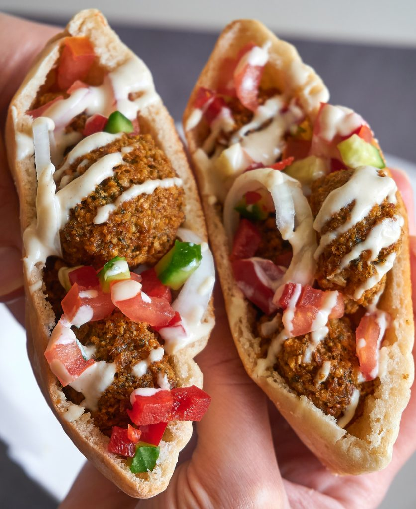 Close-up on chickpea woman holding falafel chickpea patties in pita