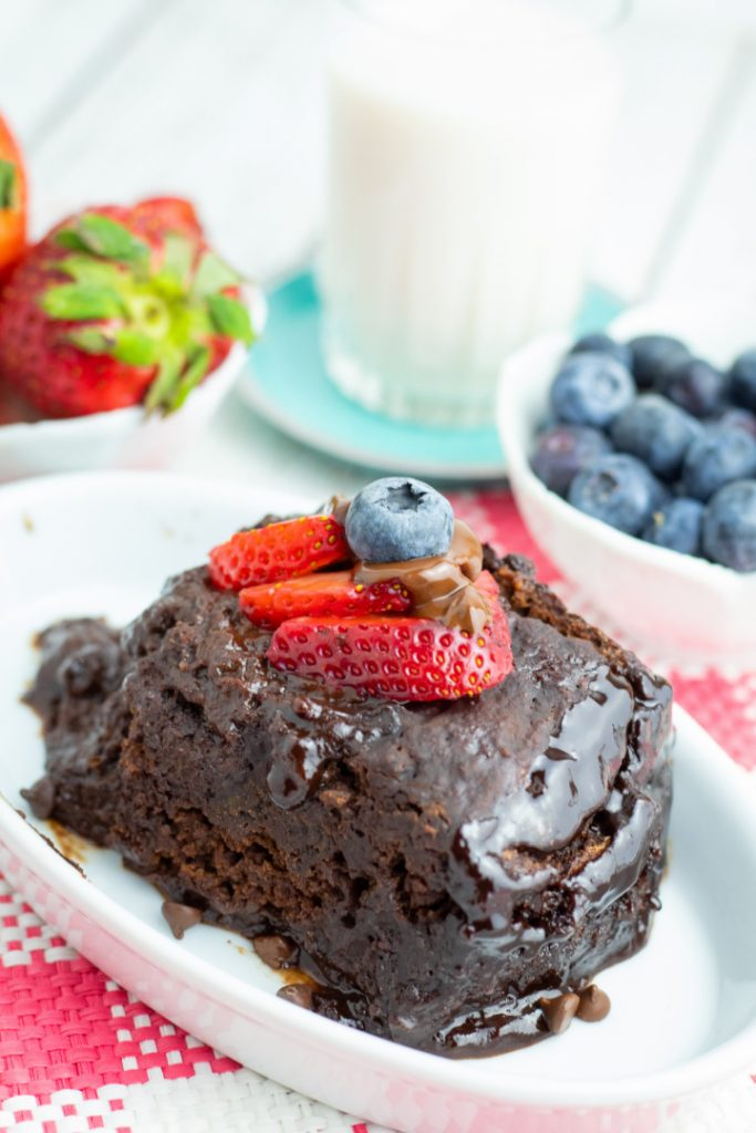 chocolate cake slice in white dish topped with strawberrie slices with glass milk and blueberries in background
