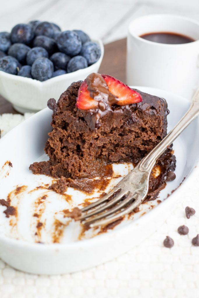 slice of crockpot chocolate cake halfway eaten in white dish with messy fork
