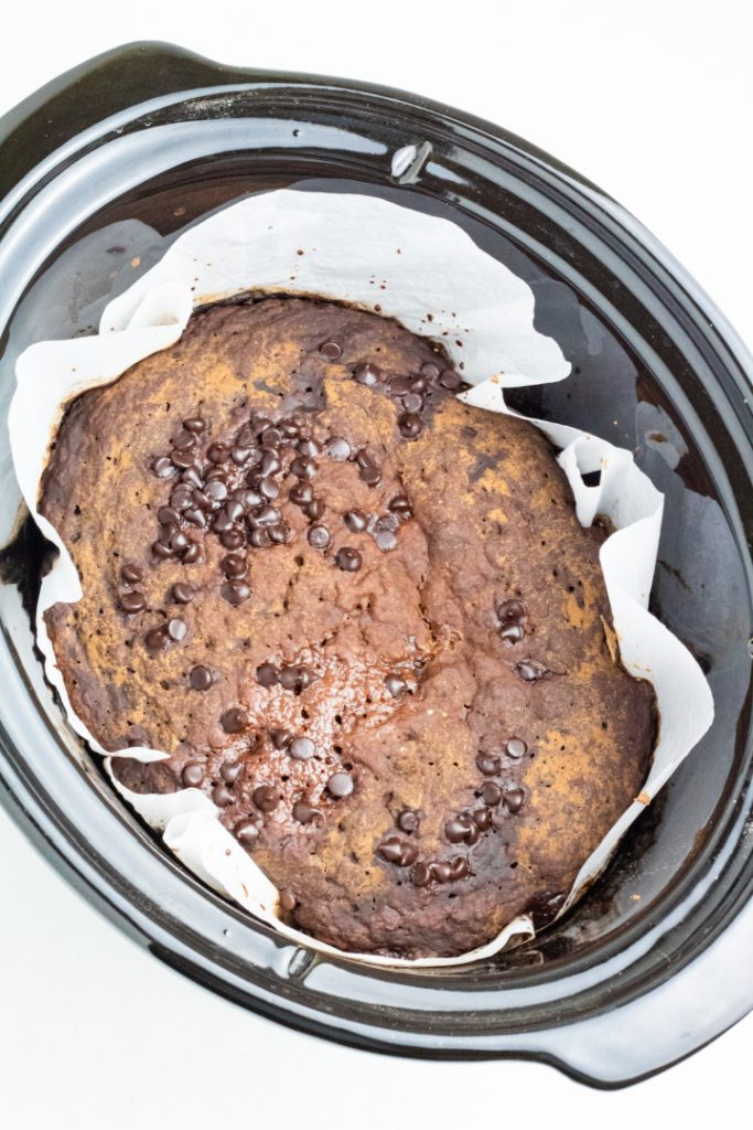 crockpot with cooked choco lava cake sprinkled with vegan chocolate chips