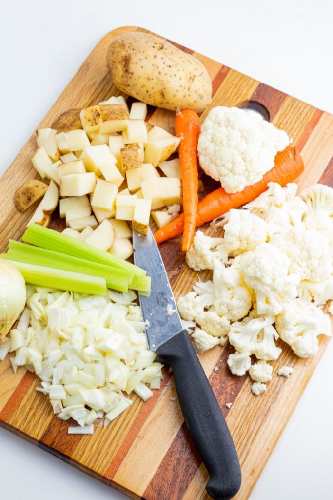 diced onions, cauliflower, potatoes, carrots, and celery on cutting board with knife