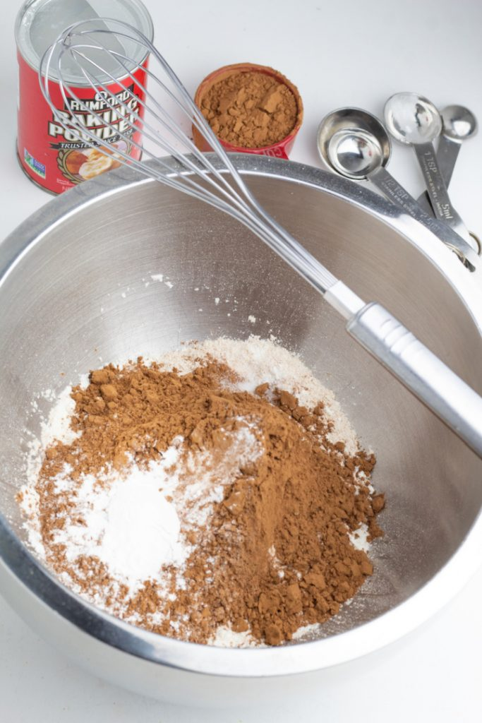 stainless mixing bowl with flour and cocoa powder with whisk